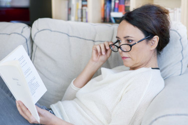 A woman wearing eyeglasses reading a book