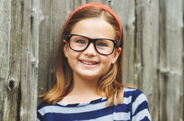 Young girl leaning on fence wearing glasses