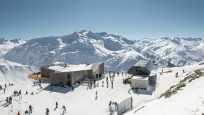 Luftaufnahme der Bergstation Gütsch mit der Gondelbahn Gütsch-Express, den mehrfach ausgezeichneten Restaurants und diversen Wintersportlerinnen und -sportler