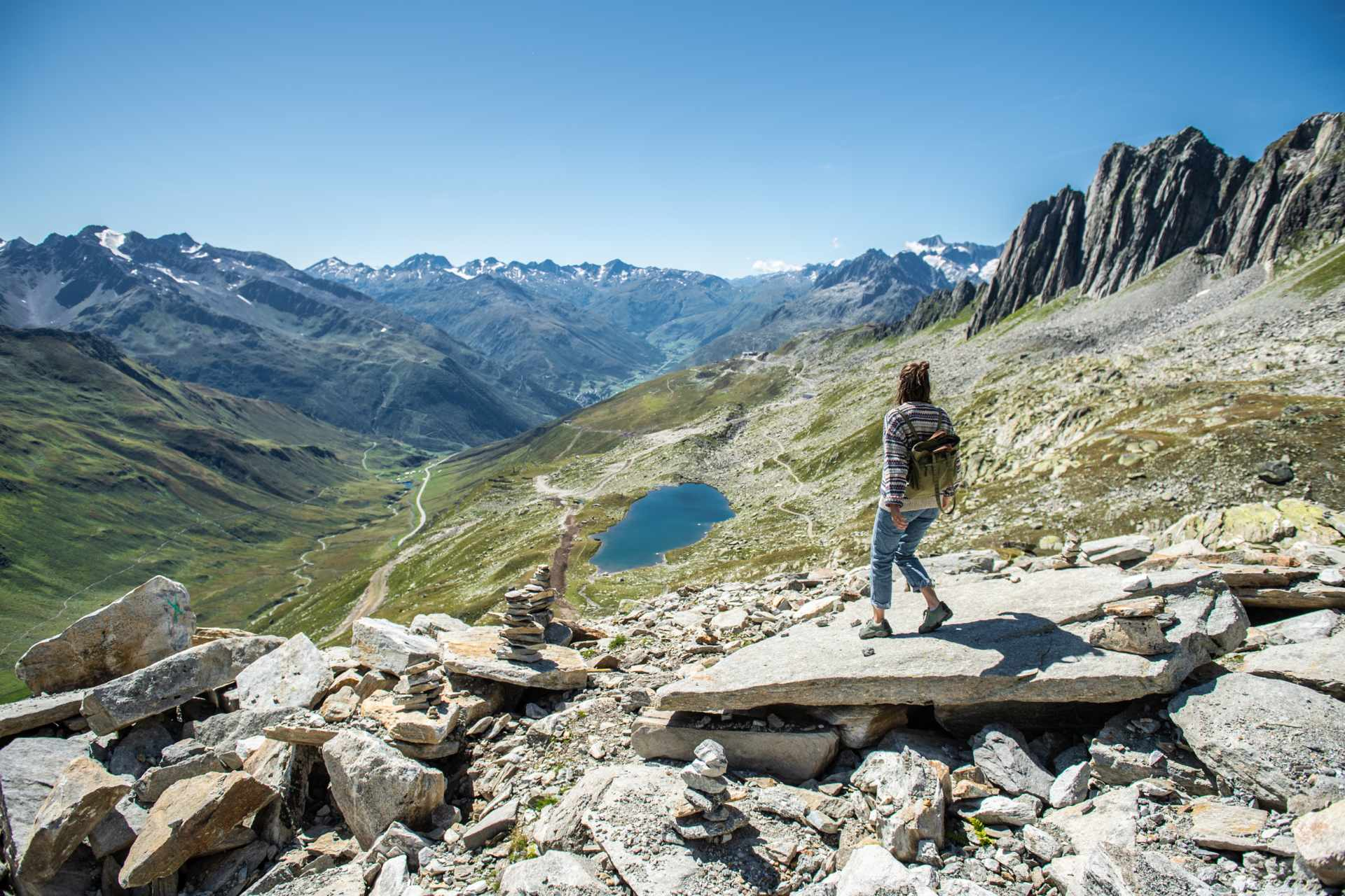 Hiker on a flat rock looking out at Lutersee in the background and view into the Urseren Valley