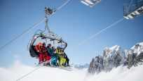 Chairlift with six winter sports enthusiasts above the clouds, heading toward Schneehüenerstock