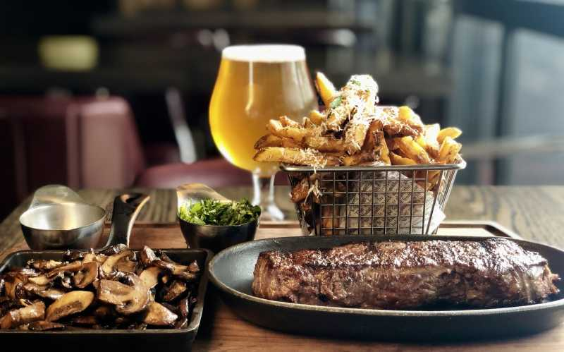 A steak with fries, fixings, and beer served at The Commoner Roncy.