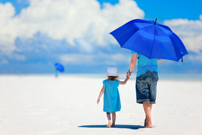 A man holding a blue umbrella walks along a beach with his daughter.