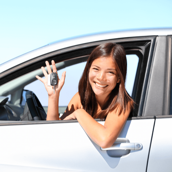 A female teen driver sitting in the driver's seat of a silver car smiling and holding the car key.