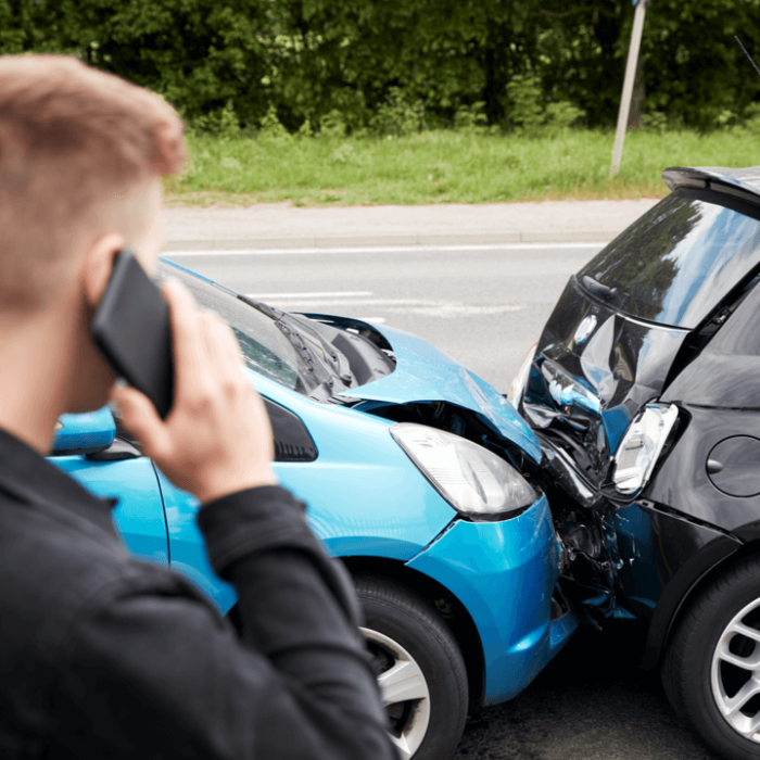 A man on the phone calling his car insurance company after a minor car accident.