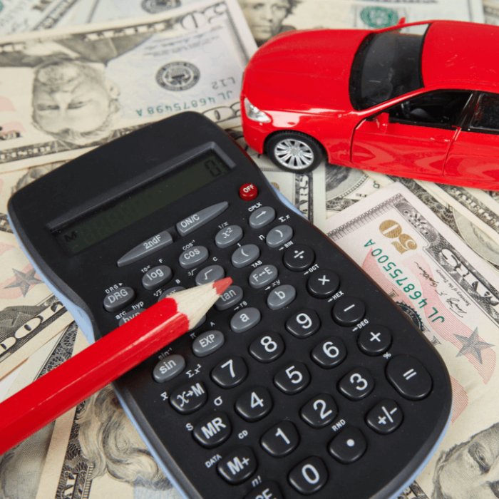 A red toy car with a calculator and red pencil sitting on top of money for a car insurance premium.