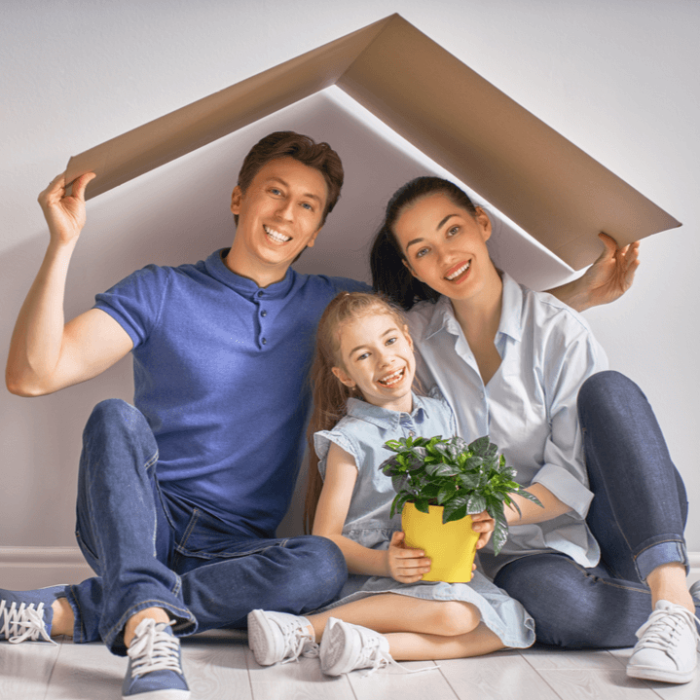 A family of three sitting on the floor in their house with a cardboard roof over their head. The roof signifies homeowners insurance coverage.