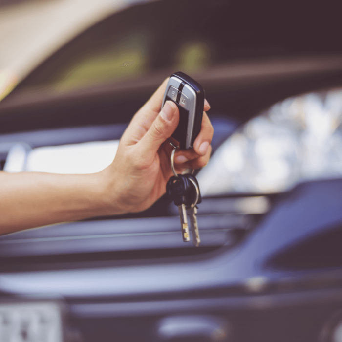 A person handing car keys over to someone who is buying a car with a salvage title.