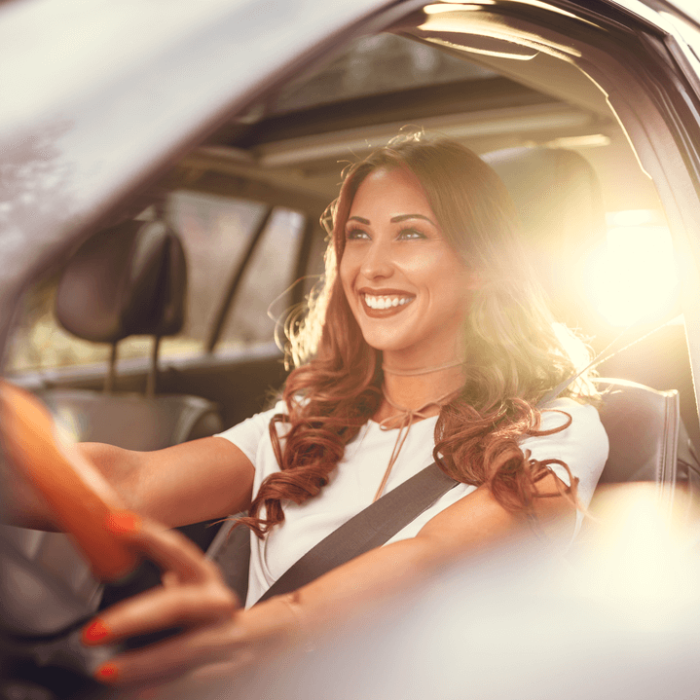 A young woman smiling and driving her car with Root car insurance.
