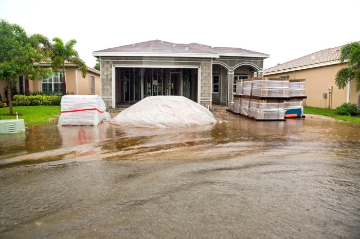 Flooded waters in front of the driveway of a home.