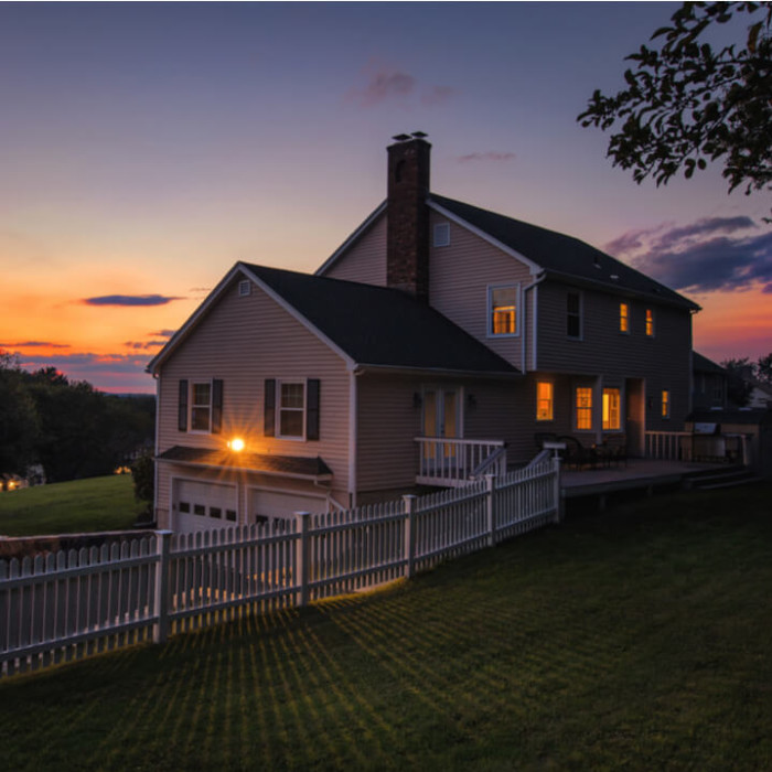 A beautiful home at sunset with cheap homeowners insurance.