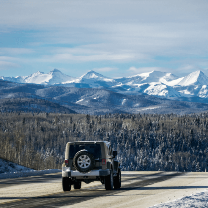 A Jeep driving down a road by the Rocky Mountains.