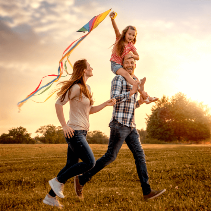 A family of two parents and one child running though a field with a kite.