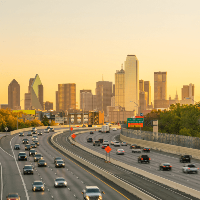 Cars driving on a highway in Dallas, Texas, at sunset.