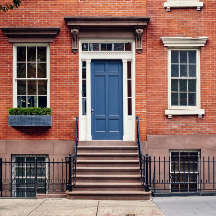 The front door of a brick house in an urban New York neighborhood.