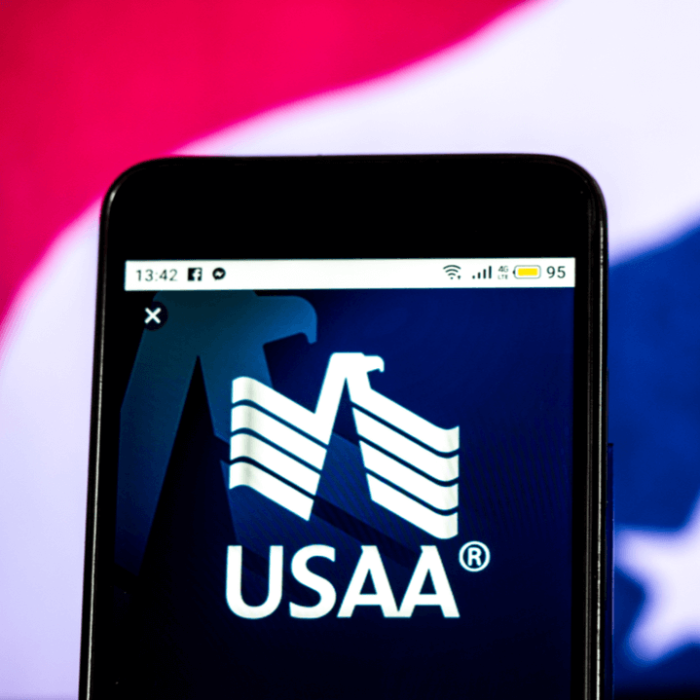 USAA mobile app on the screen of a smartphone with a flag in the background.