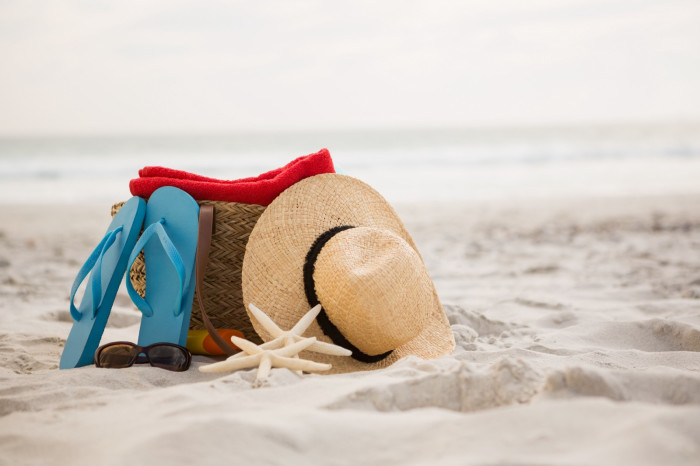 A woman's belongings on a sandy beach.