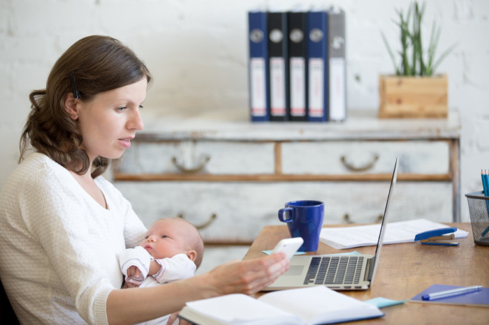 A woman holding a newborn looks at her phone.
