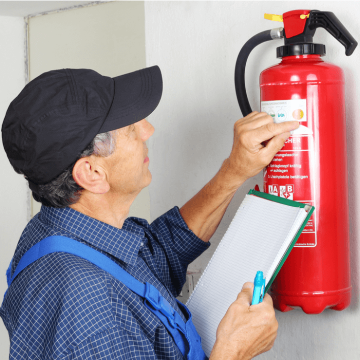 An inspector looking at the label on a fire extinguisher.