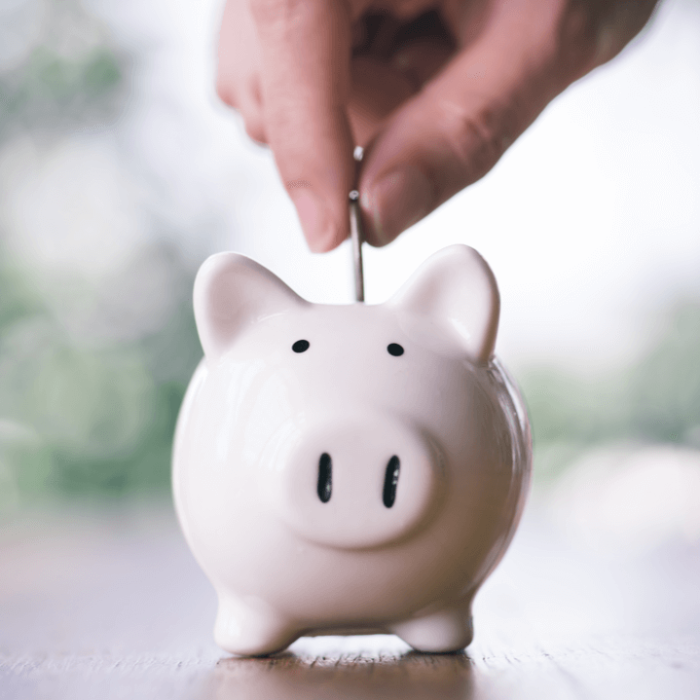 A hand dropping a coin into a light pink piggy bank to save money for self-insurance.
