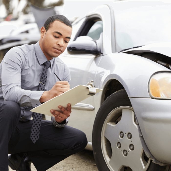 An insurance adjuster checking a car after the owner filed an insurance claim after a car accident.