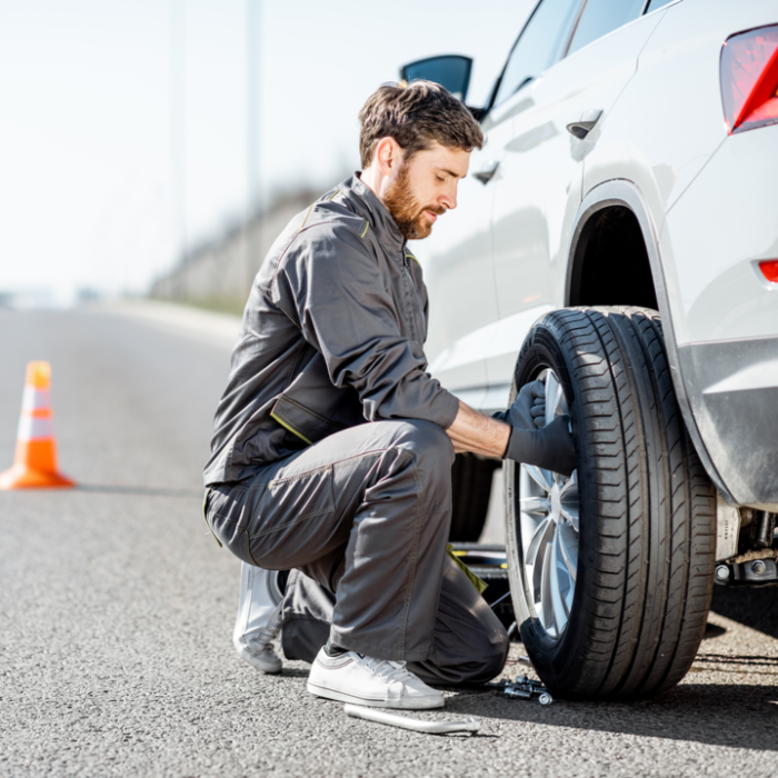 A man changing a tire on a white car on the side of the road with Progressive roadside assistance.