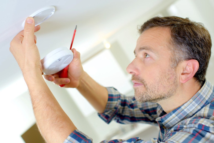 A man checks the smoke detector in his home.
