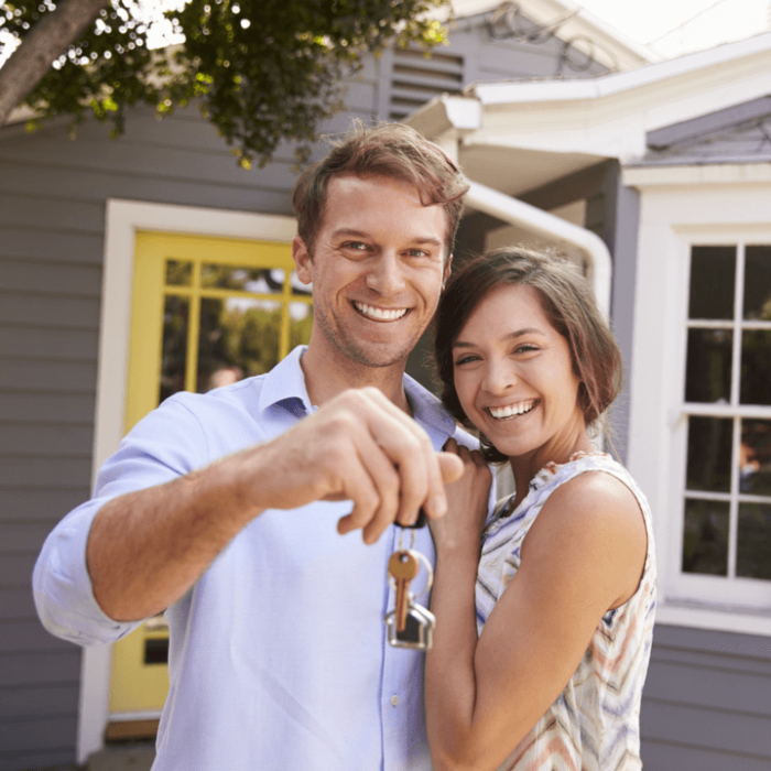 A young couple standing outside of their new house holding the house keys.