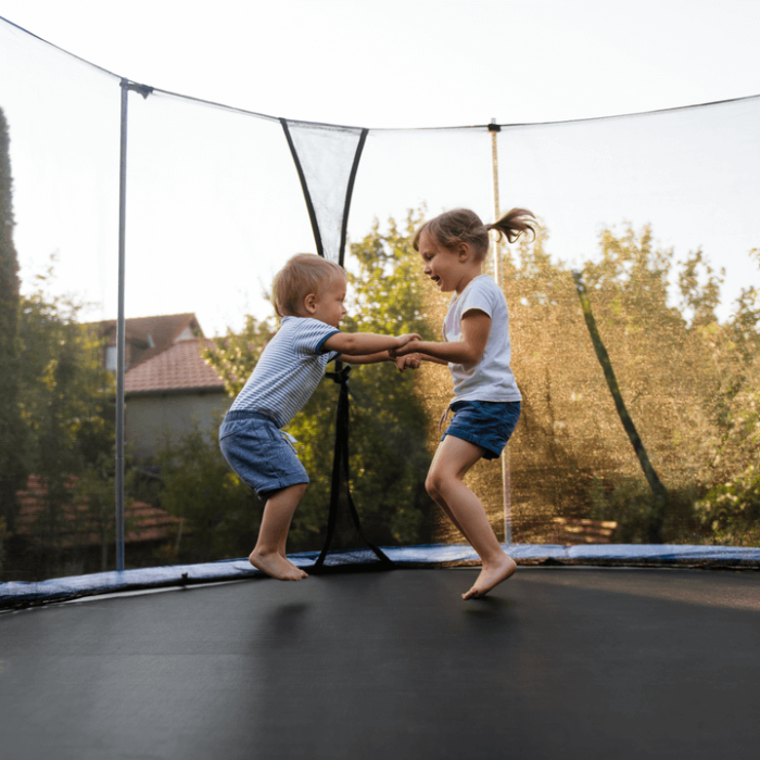 Two young kids jump on a trampoline in the back yard.