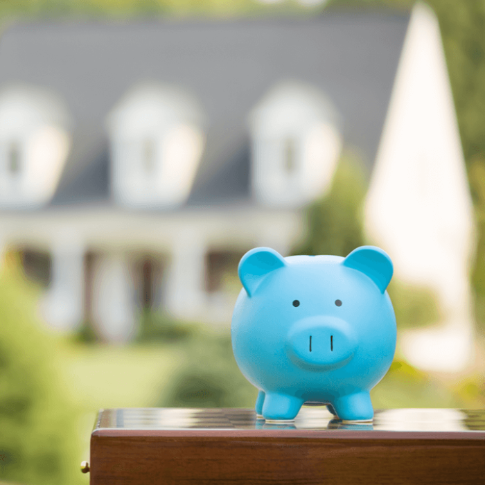 A photo of a piggy bank in front of a house to indicate saving money on homeowners insurance.