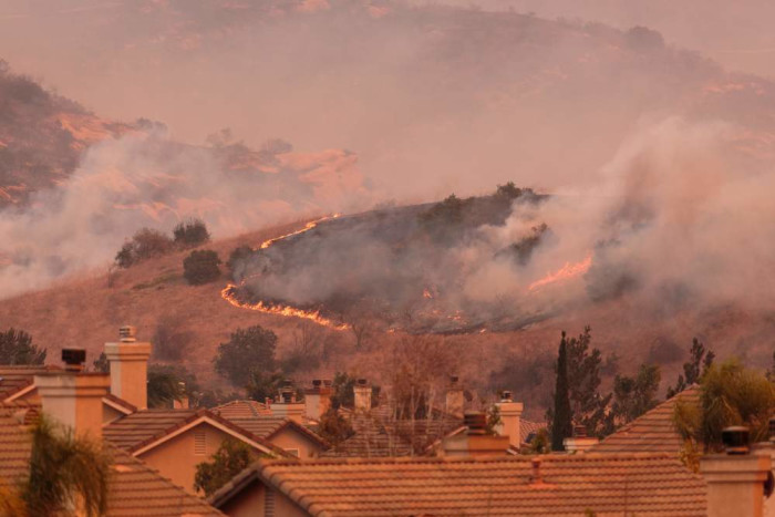 A wildfire burns land just beyond a suburban neighborhood.