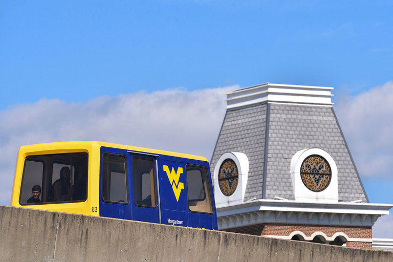 Gold and blue Personal Rapid Transit car travels on elevated guideway