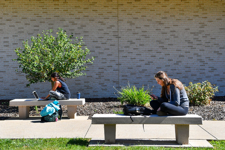 Students studying on benches outside Health Sciences