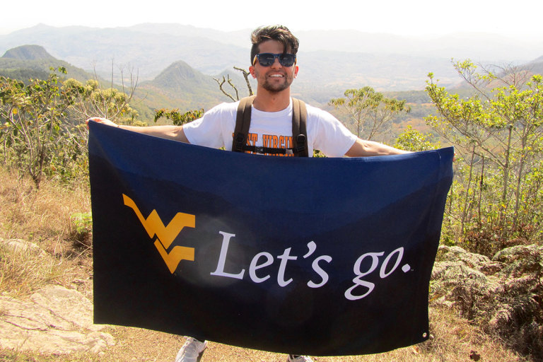 Student holds a WVU Let's Go banner in rural Nicaragua