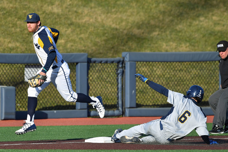 An player slides into base as a Mountaineer baseball player prepares to throw the ball.