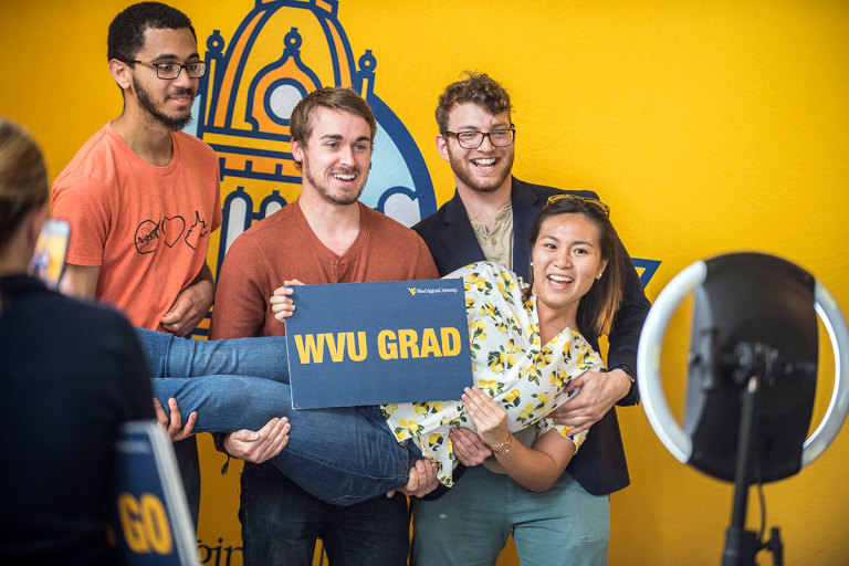 Graduates hold WVU Grad sign at photo booth for new alumni