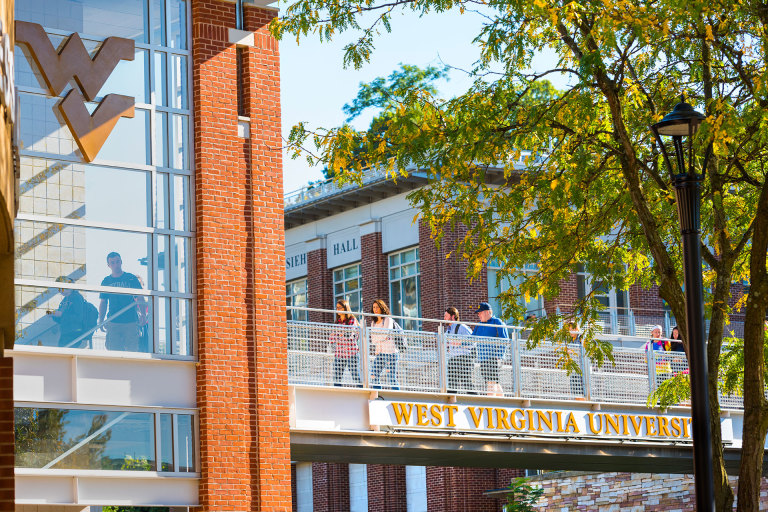 Students walk across a pedestrian bridge on the Downtown area of campus.