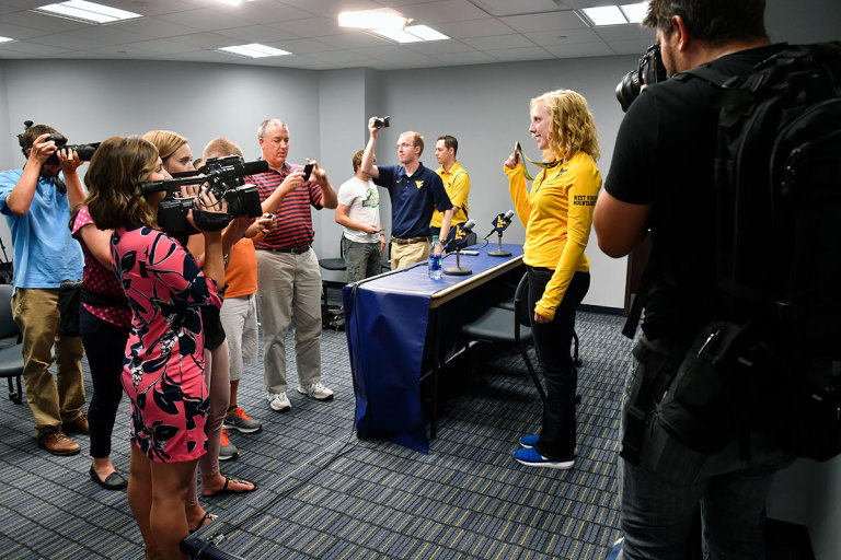Reporters surround Olympic Gold medalist and WVU rifle team member Ginny Thrasher at a press conference