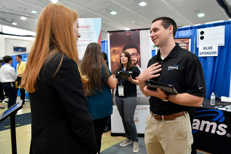 Student talks to a recruiter from Williams at a WVU career fair