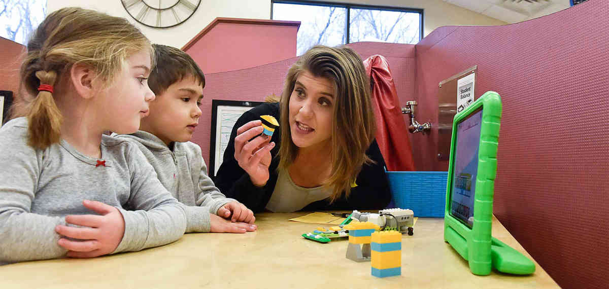 woman talking to two kids about lego robot pieces