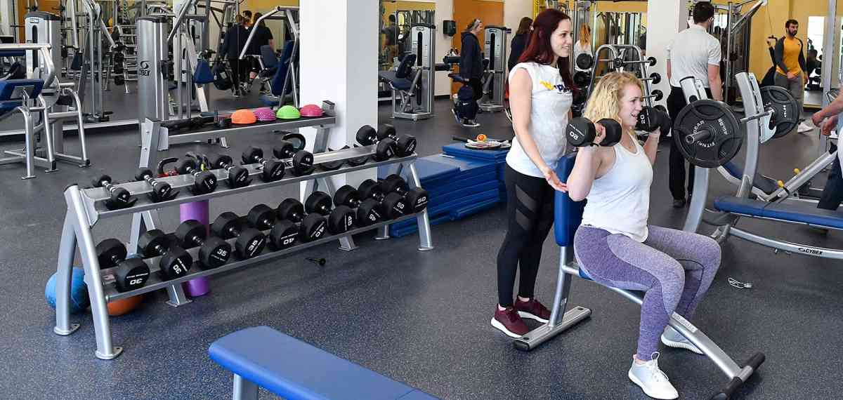 Two women lifting weights in a gym