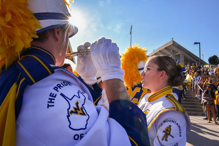 Fans watch as WVU band members warm up outside Milan Puskar Stadium