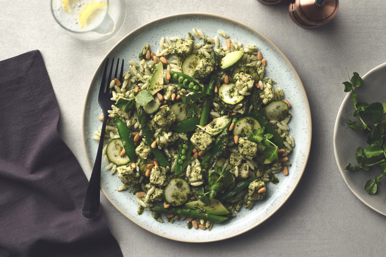 Orzo Pasta with asparagus, zucchini, sugar snap peas, avocado, Quorn Pieces, and pesto topped with pine nuts.