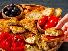 Quorn Meatless Mozzarella and Pesto Cutlets on a platter with tomatoes and olives