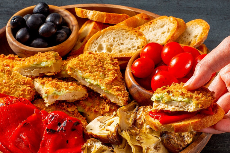 Quorn Mozzarella and Pesto Escalopes on a platter with tomatoes and olives