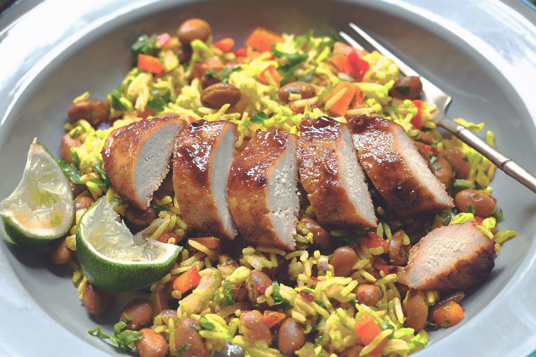 A sliced Quorn Fillet topped with glaze atop a bed of rice with beans and peppers with two wedges of lime on the side.