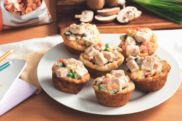 Mini Quorn Piece pot pies with carrots, peas, and corn on a white plate.