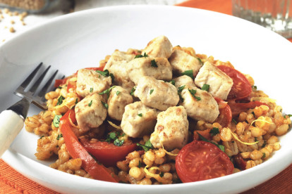 Vegetarian meal made with Quorn Pieces, pearl barley risotto, tomatoes and red pepper served in a white bowl with fork next to a glass of water.