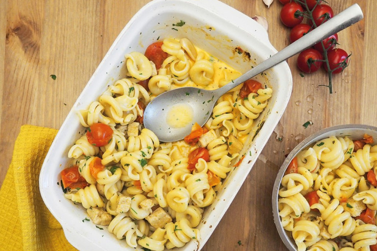 Baking dish of pasta with cherry tomatoes and baked quorn pieces; sprinkled with herbs