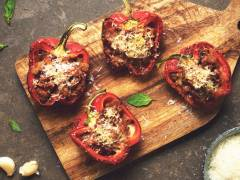 Four baked red peppers stuffed with Quorn Grounds and topped with cheese on a wooden cutting board with basil leaves scattered around.